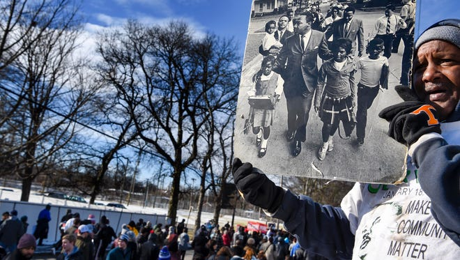 Kenny Cobington holds a picture of Martin Luther King Jr. marching as the hundreds march down Jefferson Street to celebrate what would have been Martin Luther King Jr.'s 89th birthday in Nashville, Tenn., Monday, Jan. 15, 2018.