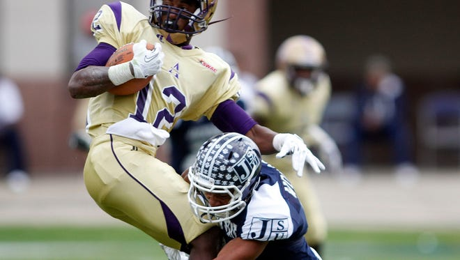 Jackson State's Travis Woods  wraps up Alcorn State's Brandon Vessell during a game on December 2013 in Jackson.