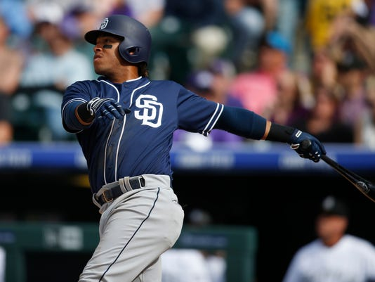 San Diego Padres' Yangervis Solarte follows the flight of his double to drive in two runs off Colorado Rockies relief pitcher Chris Rusin in the fourth inning of a baseball game Friday, April 8, 2016, in Denver. (AP Photo/David Zalubowski)
