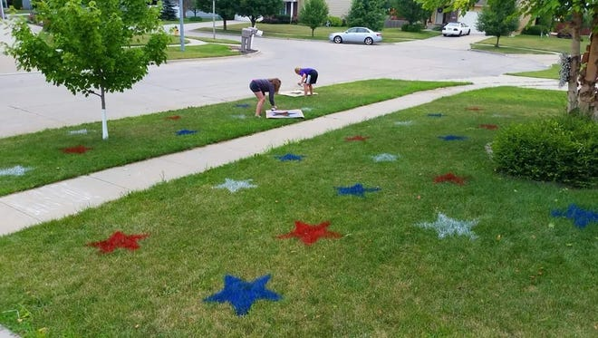 Ten-year-olds Ella Harris and Cassie Johnson spray-paint red, white and blue stars on the Harris family home on Northwest Ridgeline Drive in Ankeny for the Fourth of July in 2016.