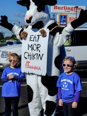 Anna Gronowski, 6, left, and her sister Emma, 5, get a photo taken with Cow the mascot of the Chick-fil-A chain restaurant Saturday, Oct. 8, 2016.