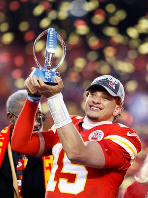Kansas City Chiefs' Patrick Mahomes holds up the Lamar Hunt Trophy after the NFL AFC Championship football game against the Tennessee Titans Sunday in Kansas City, MO. The Chiefs won 35-24 to advance to Super Bowl 54.