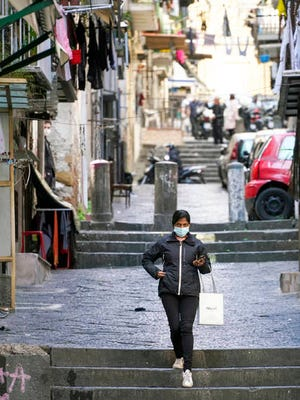 A woman walks in a street of Naples on Monday. Region Campania allowed cafes and pizzerias to reopen for delivery Monday, as Italy it is starting to ease its lockdown after a long precautionary closure due to the coronavirus outbreak.