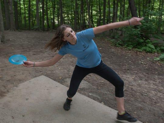 Chelsie Huz launches a disc toward a distant basket.
