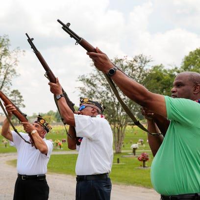 Mayor Reginald Tatum, (right), shoots a rifle during