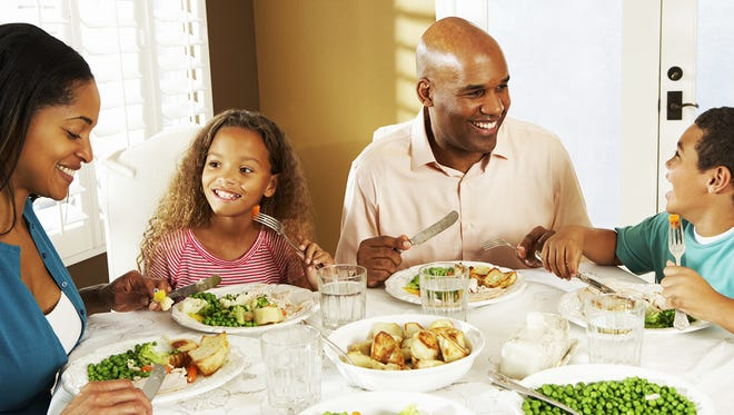 Establish a family habit of eating together at the dinner table; it's just one way to teach your kids healthy eating behaviors.