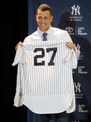 New Yankee Giancarlo Stanton with his jersey during the winter meetings in Orlando, Fla.