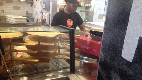 Pressing the crust at Blaze Pizza.
