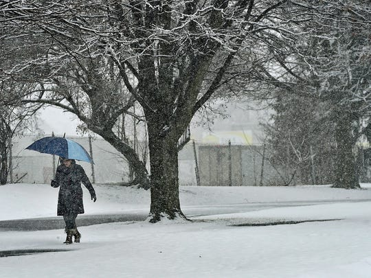 Karen Vanier takes a morning walk at Chambersburg Memorial Park despite steady snowfall Tuesday, Feb. 9, 2016. Colder temperatures are forecasts for the region.