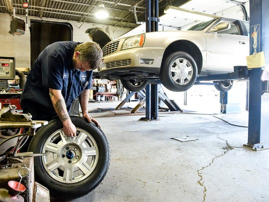 Tony Wiseman performs maintenance on a customer's tire in the garage of Family Tire on Tuesday morning.