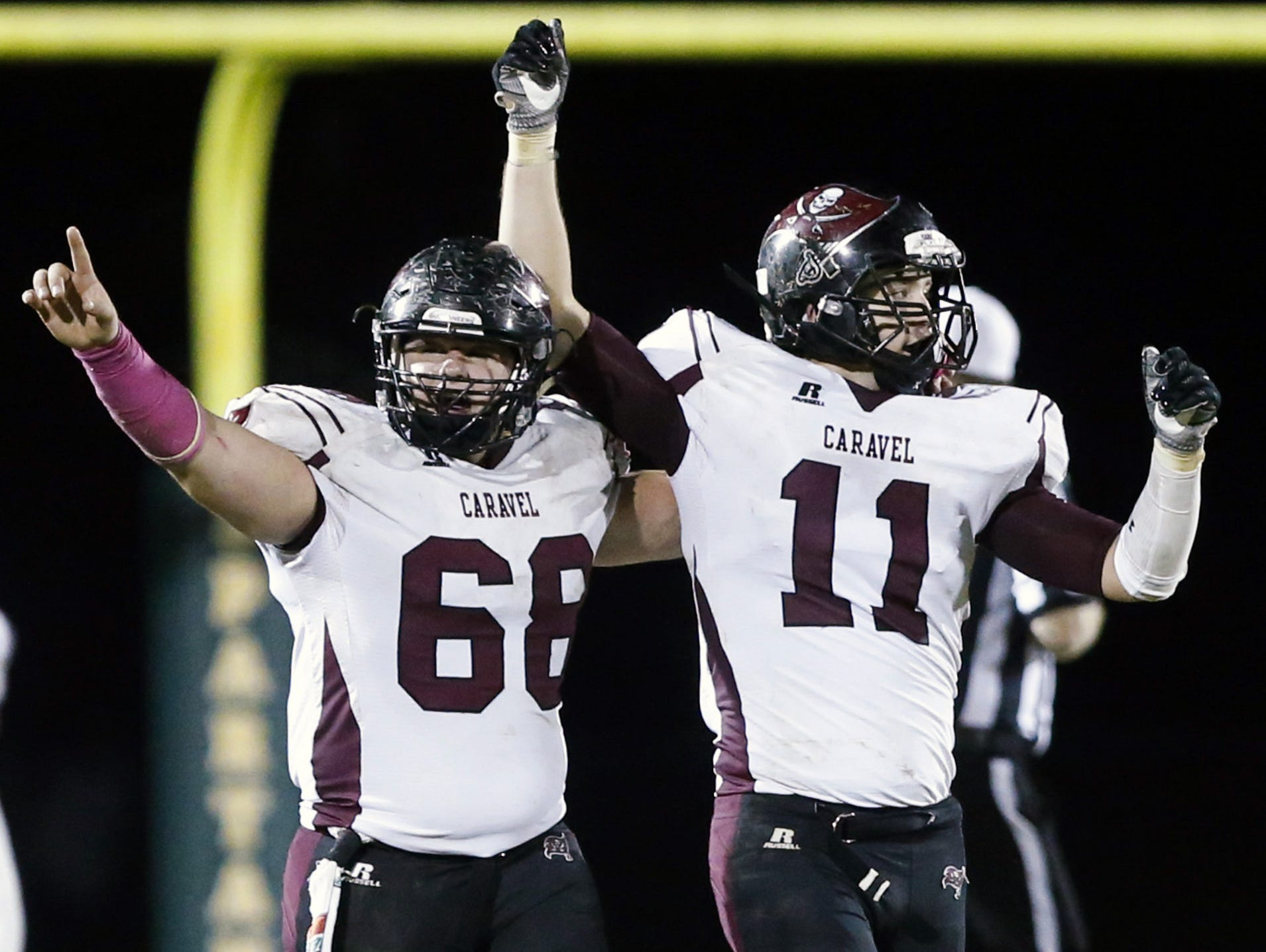 Caravel's Jacob Reed (left) and Matt Bowe celebrate after the Buccaneers edged St. Mark's 7-0 on Oct. 14. Brad Myers is picking Caravel to win a close game at Cape Henlopen on Friday, while Matt Kalin predicts the Vikings will prevail.