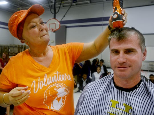 Fifth-grade teacher Marsha Sanderson cuts the hair of the Thelma Barker Elementary School Principal Ryan Kirkbride. Kirkbride told students and Sanderson, who is taking chemotherapy for ovarian cancer, that if they surpassed their Relay for Life fundraising goal, he would have his head shaved.
