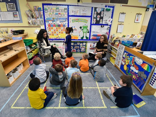 Classroom teacher Nicole Cardinale, left, and paraprofessional Julie Poore, right, work with their class on learning how to read a calendar at Appoquinimink Preschool Center in Middletown.