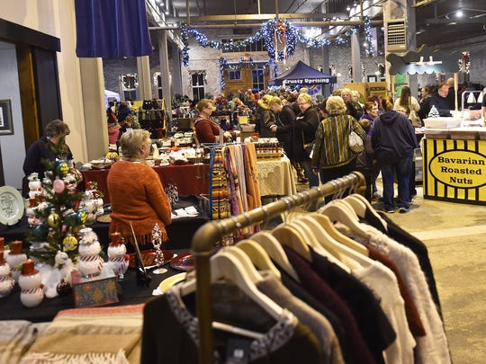 Shoppers browse vendors carrying holiday gift items at an area craft market.