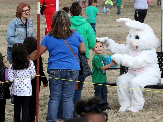 Families stand in line to take a photo with the Easter
