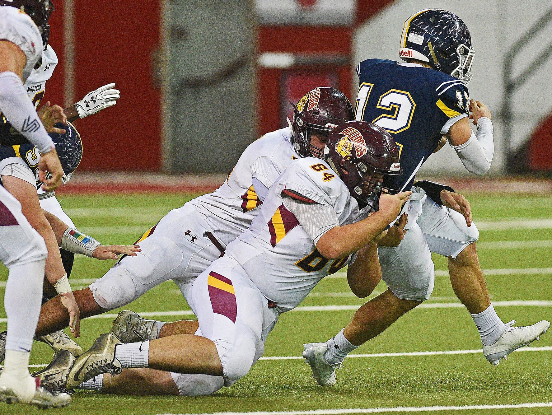 Tea Area's Payton Conrad (12) is brought down by Madison's Brad Hoff (64) and Nate Huthmiller (71) during the 2016 South Dakota State Class 11A Football Championship game Saturday, Nov. 12, 2016, at the DakotaDome on the University of South Dakota campus in Vermillion, S.D.