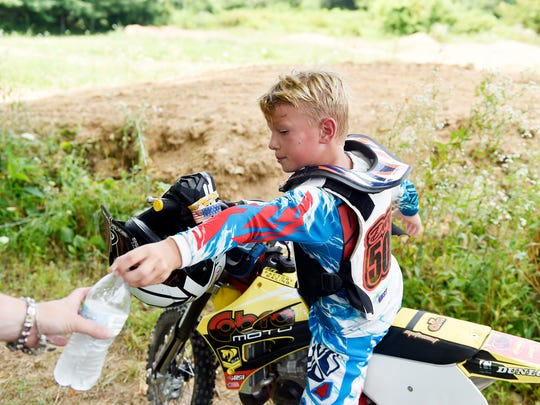 Parker Dwyer, 9, hands back a water bottle to his mother