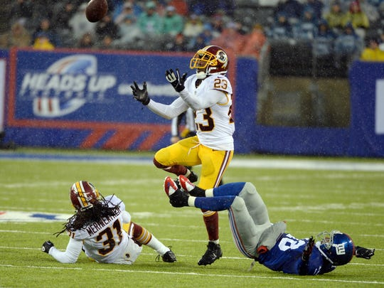 Washington Redskins cornerback DeAngelo Hall (23) breaks up a pass to New York Giants wide receiver Louis Murphy (18) on the turf of New Jersey's MetLife Stadium during a December game.