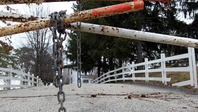 A locked gate blocks the driveway of the former Campbell Lodge, Cold Spring. The property remains vacant three years after the state shut down the facility for alleged mistreatment of residents.