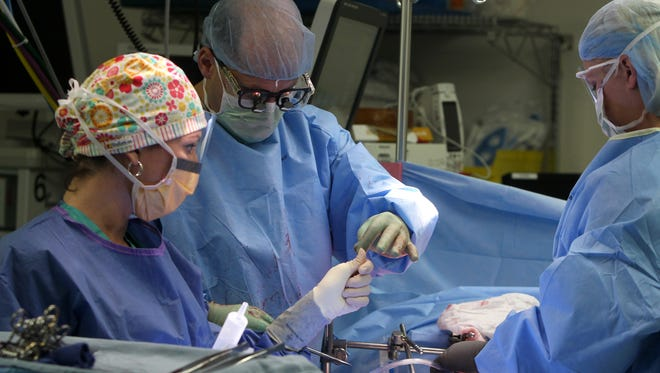 Laurie Ford, Dr. Mark Bloomston and Meagan Fay perform surgery Tuesday at Lee memorial Hospital in Fort Myers.