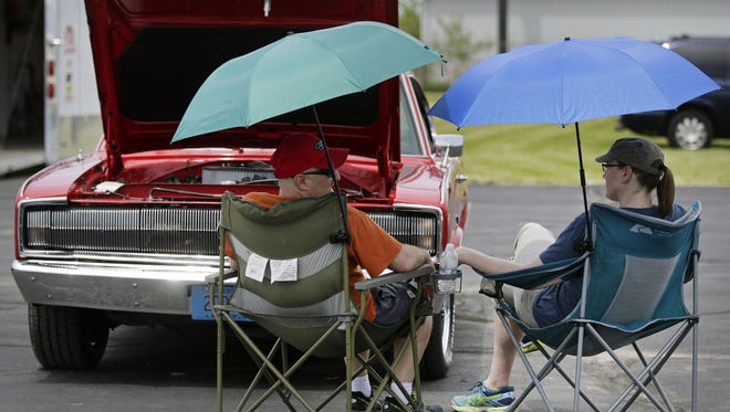 Jeff Bork and Laura Zuleger pass the time with a 1966 Dodge Charger during the Neenah American Legion Memorial Day Car Show and Picnic on May 28 at the Neenah Labor Temple.