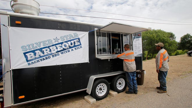 Eric Espinoza, left, and Tony Mitchell wait for their orders  July 9 at the Silver Star Barbecue food truck in the Smith's parking lot off 20th Street in Farmington.    cq