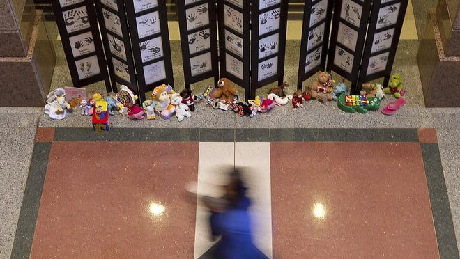 A passerby is shown in 2011 walking past a portion of a memorial at the state Capitol honoring Texas children who have died from abuse or neglect. In the nine months ending April 30, 2020, 11 foster kids died in the state's care.