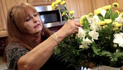 Laura Kiefert, who has difficulty standing for long periods because of chronic leg pain related to her diabetes, arranges a vase of flowers in her kitchen July 11, 2018 in Howard, Wis.