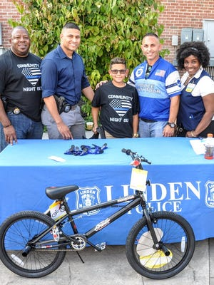 Linden Lt. Abdul Williams, Officer John Vasquez, Jeremiah Arellano, Linden Lt. Joe Cacioppo and Walmart representative Angela Wilson present the bicycle during National Night Out.