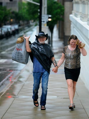Tourists Erik and Nina Mikklsen of Bergen, Norway, where they say it rains 90 percent of the time, enjoy a walk in the rain back to their hotel near the state capitol Sunday, May 17, in Nashville.