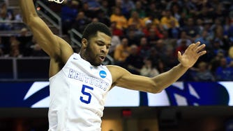 West Virginia Mountaineers forward Jonathan Holton (1) tries to shoot while guarded by Kentucky Wildcats guard Andrew Harrison (5) during  the semifinals of the midwest regional of the 2015 NCAA Tournament.