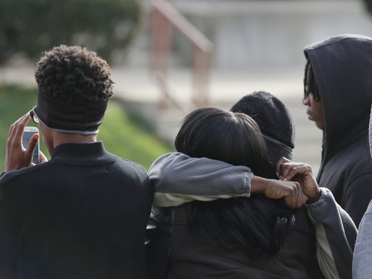Friends and relatives comfort each other during a stand