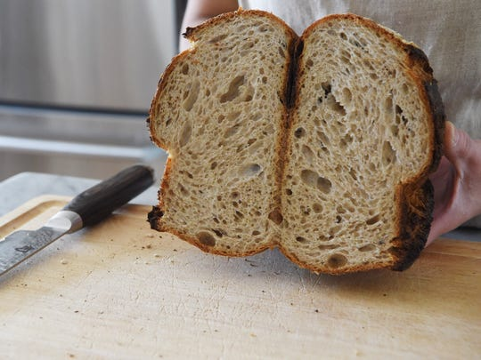 Cynthia Kinahan, owner of Pawling Bread Company, displays the inside of one of her country sourdough loaves at her home in Pawling.