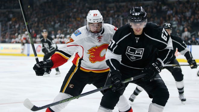 Calgary Flames center Derek Grant, left, and Los Angeles Kings center Nic Dowd, right, skate to the puck during the first period of an NHL hockey game, Thursday, March 31, 2016, in Los Angeles. (AP Photo/Danny Moloshok)