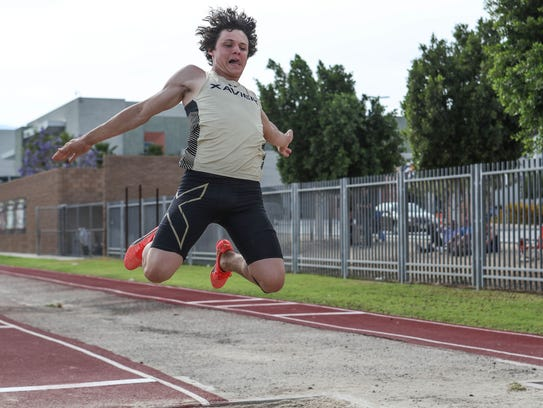 Chandler Barbato jumps in the long jump during the