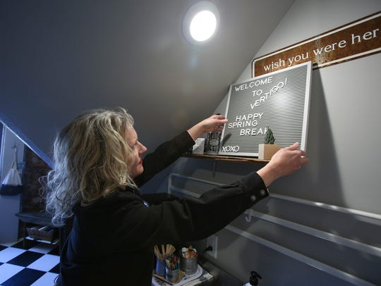 Dana McMahan hangs a welcome sign in the kitchen of