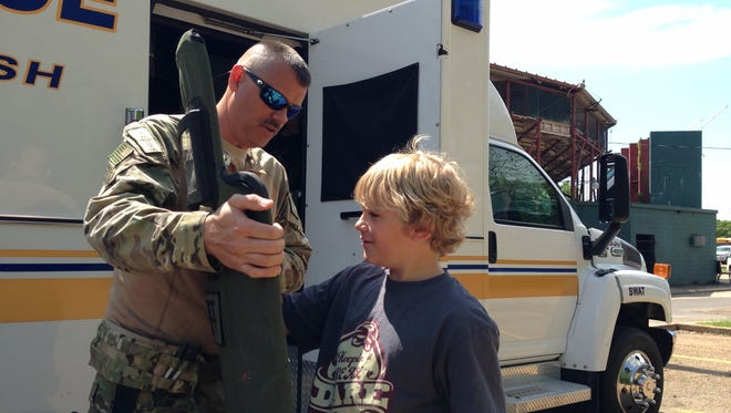 Shane Kessler (left), a medic with the Rapides Parish Sheriff's Office SWAT, shows 10-year-old Evan O'Brien a piece of equipment from the office's tactical response vehicle Tuesday. Evan was one of about 600 students touring such displays on Tuesday.