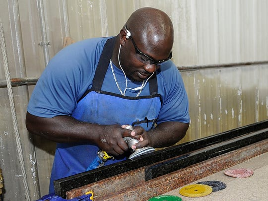 Cornelius Pitts a fabricator with Stone Innovations in Plover works on a piece.