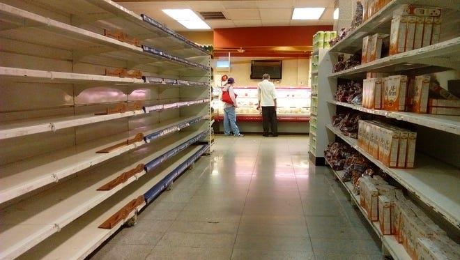 Mostly empty shelves of a supermarket is pictured in Caracas on May 28, 2016.  The shortage of basic foodstuffs in Venezuela exceeds 80%, a survey revealed.