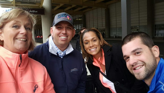 Blue Wahoos team president Jonathan Griffith (center) with team vice president Donna Kirby (left), director of retail operations Denise Richardson, and former stadium operations trainee Trevor Matifes outside of Gaylord National Resort and Convention Center at the Baseball Winter Meetings in National Harbor, Maryland.