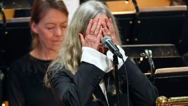 Patti Smith covers her face when performing 'A Hard Rain's A-Gonna Fall' by absent 2016 Nobel literature laureate Bob Dylan during the 2016 Nobel prize award ceremony at the Stockholm Concert Hall on Saturday.