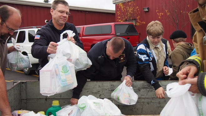 The Fond du Lac Fire Department help youth from Boy Scout Troop 701 unload vehicles during the organization's annual food drive.  Fond du Lac area residents left donated food items at their doorsteps or mailboxes for the scouts to pickup. Food was then taken to The Salvation Army where volunteers were on hand to unload.