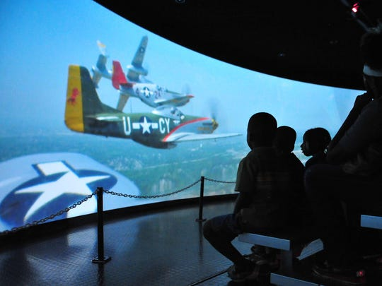 """Visitors watch the movie """"Rise Above"""" in the CAF Red Tails Squadron traveling exhibit."""