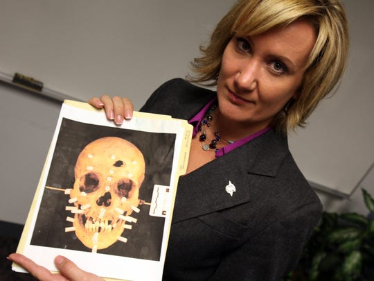 Sarah Krebs, with the Michigan State Police, holds a photocopy of the skull of an unidentified homicide victim found in a shallow grave on Detroit's west side in 2008.