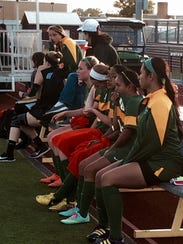 The Indian River girls soccer team looks on from the