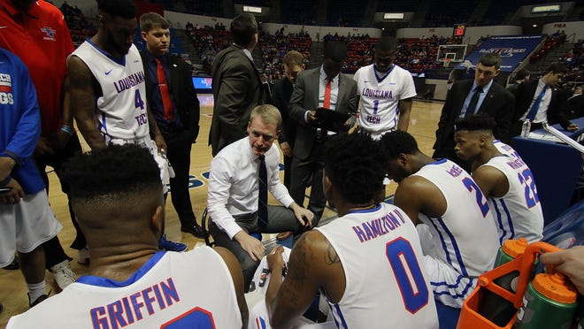 Louisiana Tech coach Eric Konkol, center, talks to his team during the huddle of the Conference USA opener against Southern Miss.