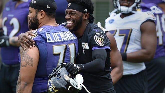 Baltimore Ravens quarterback Robert Griffin III, right, hugs Jermaine Eluemunor before NFL football practice, Thursday, May 23, 2019, in Owings Mills, Md. (AP Photo/Gail Burton)