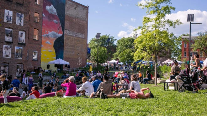Festival goers relax on the Safe Harbors Green at the Newburgh Illuminated Festival during a previous year.