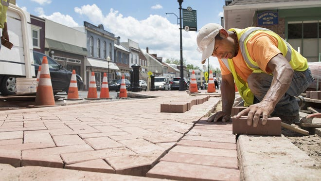 Workers build a new brick crosswalk on High Street at Commerce Place in Mount Holly on Friday.  Mount Holly Township is embarking on the final phase of improvements to their Downtown Business district.
