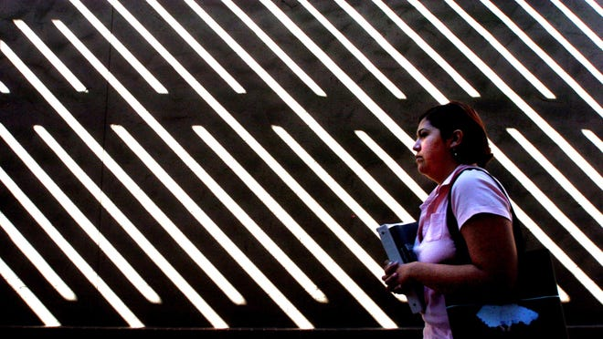 A San Joaquin Delta College student is caught up in the pattern of shadows created by a trellis shade structure in an alley between Danner Hall and Shima Center on the Delta campus in Stockton.